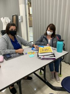 Mrs. Lloyd and Mrs. Pierson partner up to model making a word activity with Jan Richardson's Guided Reading book available as a reference.