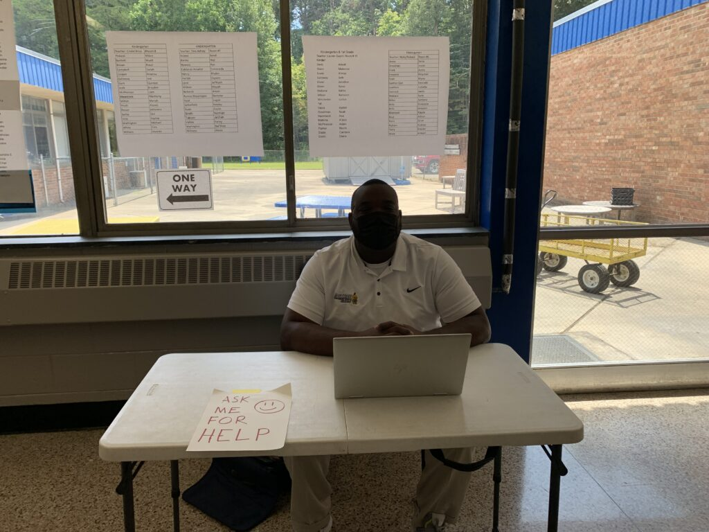 Mr. Cook, physical education teacher, was ready to assist parents who needed support finding their children's classrooms.