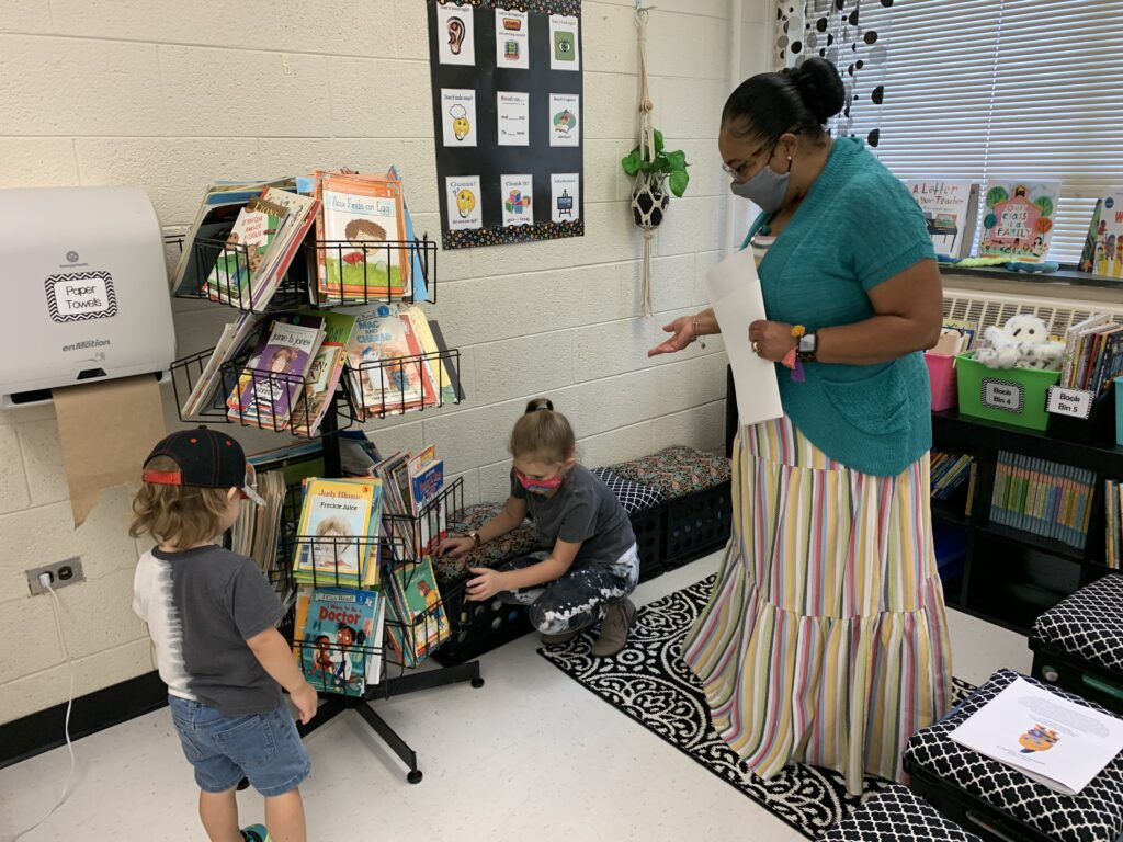 Mrs. Gilmore was showing students the variety of books she had in the classroom.