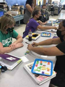 Teachers shown partner up to model making a word activity.