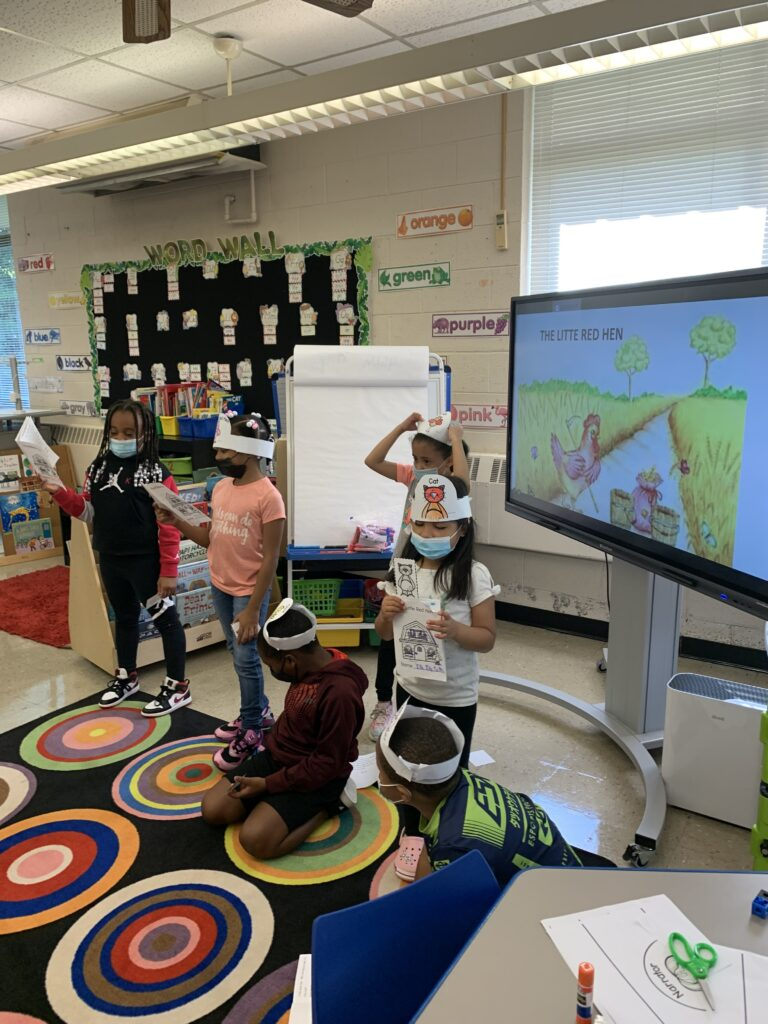 Students followed along with the text and stood for their parts of the play.